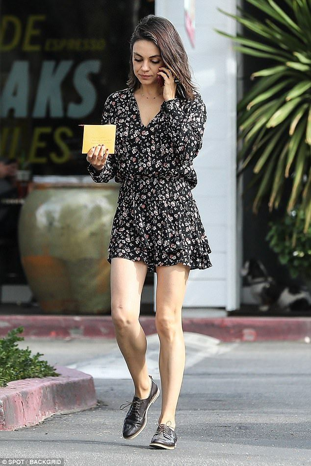 The gorgeous actress Mila Kunis is walking in the street